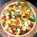 A top down view of corn avocado salad. Salad has lots of tomatoes, corn, garbanzo bean pasta shells, and basil.